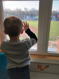 A young child looks out the window of Cam's Clubhouse at Kannapolis Intimidators Minor League Baseball Ballpark