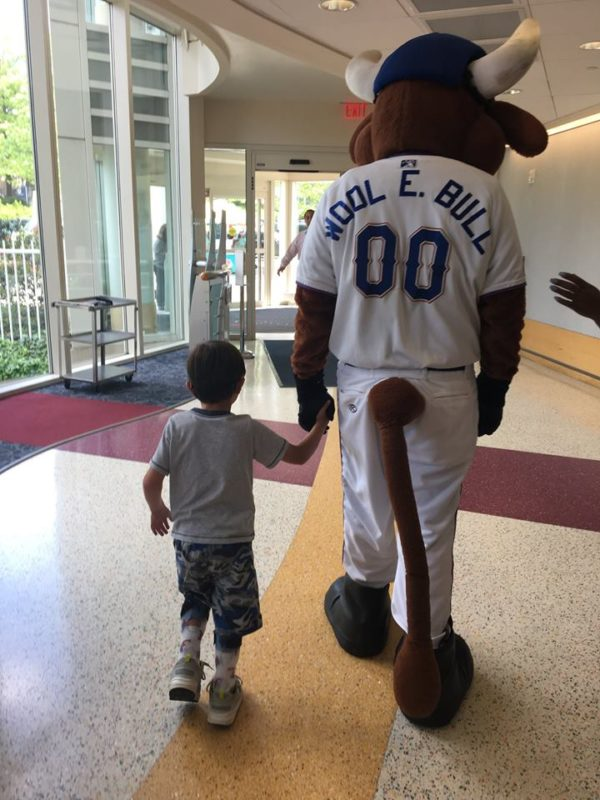 Wool E. Bull walks with a child at a community event.